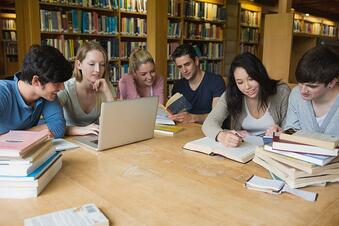 Students sitting at a table in a library while learning and working on a laptop